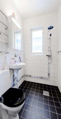 Banheiro preto e branco com piso preto