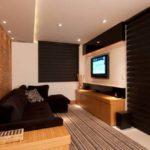 sala decorada com papel de parede e sofá preto