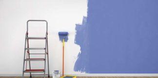 parede meio pintada de azul, com rolo e escada