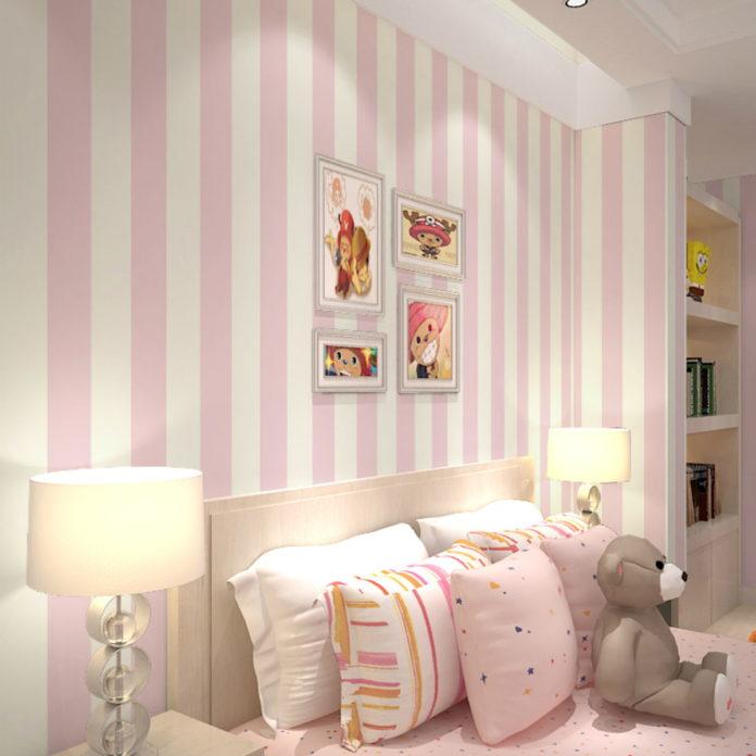 quarto de menina com papael de parede listrado em rosa e branco, com quadros decorativos