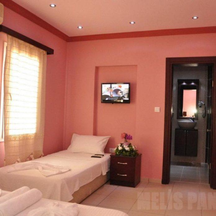 quarto decorado com duas camas de solteiro e paredes na cor salmão