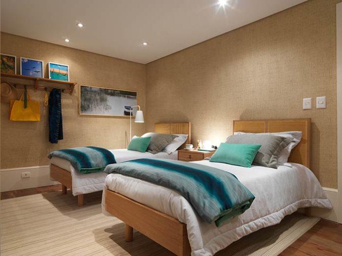 quarto de visita decorado e com duas camas de solteiro