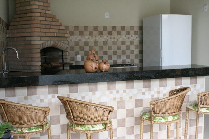 área de churrasqueira rústica com bancada em granito
