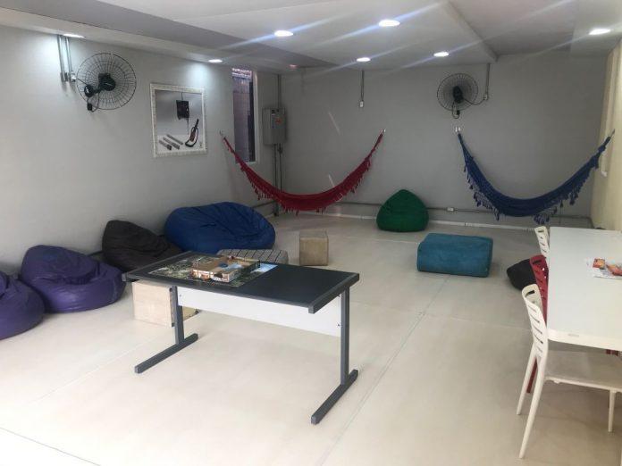 Sala de descanso para o ambiente de trabalho com puffs e rede de descanso