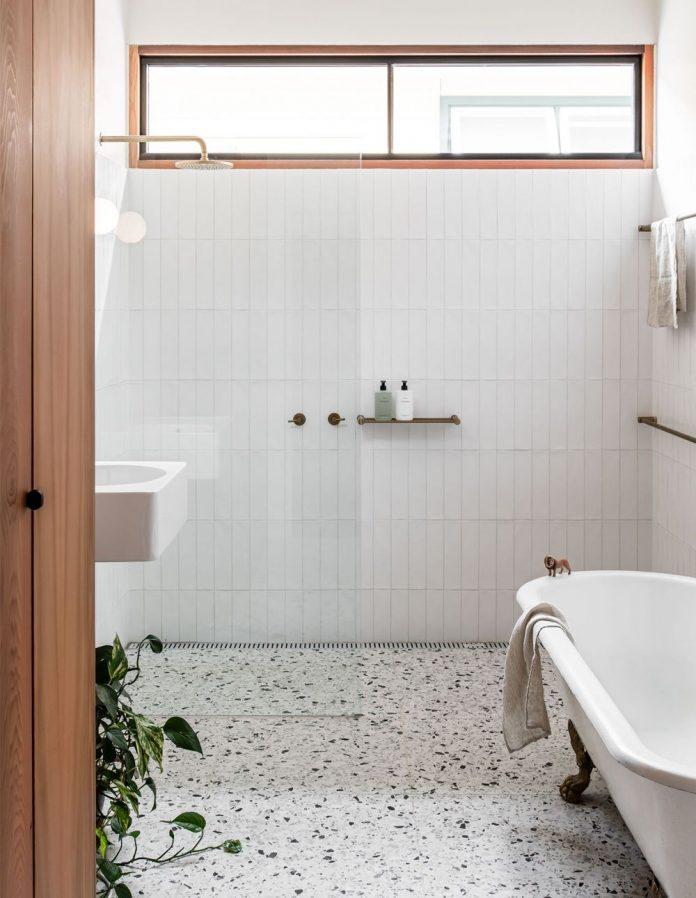 banheiro branco com granilite no chão do banheiro