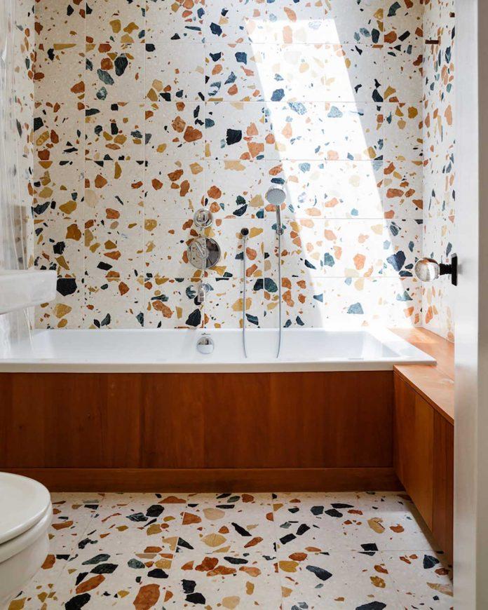 banheiro com granilite mais alegre com pedras maiores e coloridas tanto no chão quanto na parede e para dar um contraste e combinar uma banheira com revestimento em madeira