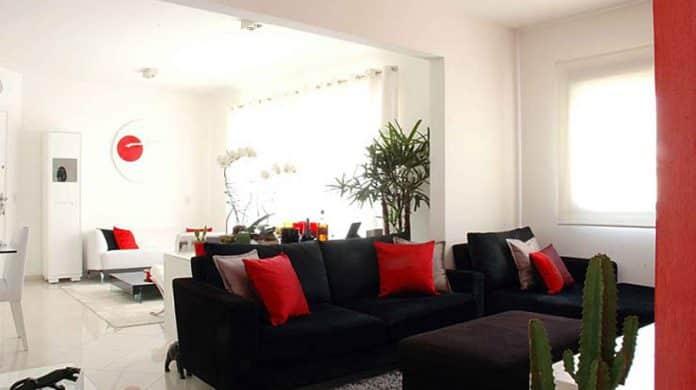 ambiente todo branquinho sendo que só o sofá é preto e as almofadas vermelhas