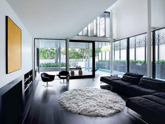 ala super luxuosa, onde tanto o sofá quanto o piso são pretos e a parede e o tapete são brancos para fazer um contraste e não deixar o ambiente tão pesado
