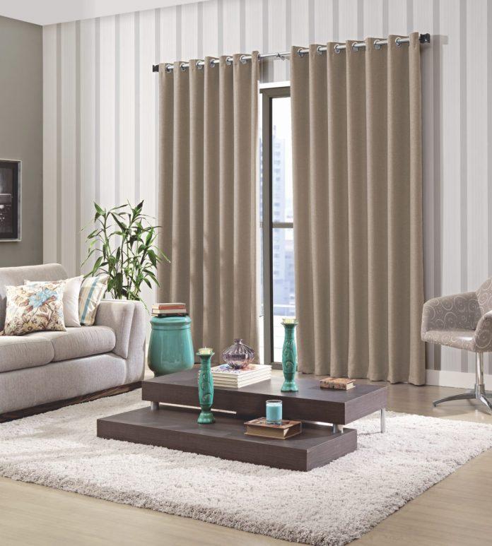 uma sala que explorou bem o nude o utilizando na cortina e móveis como o sofá, para trazer um pouco mais de cor e quebrar um pouco o nude se usou uma mesa central de um marrom mais escuro