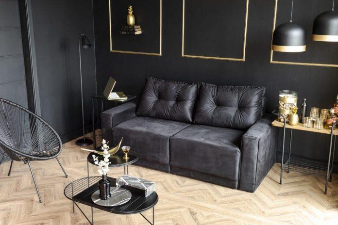 sala que não é tão grande e usou tanto a parede na cor preta como os principais móveis sofá, mesinha, banco