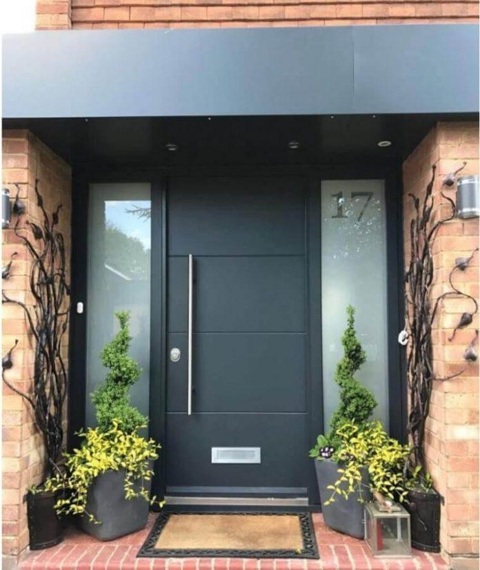 uma entrada onde a porta é preta e está em harmonia com o conjunto, usou um tapete e vasos de plantas para ajudar a compor a entrada e trazer ainda mais beleza.