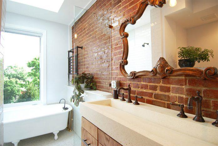 tijolinho tendendo ao luxo, onde se fez uma parede central utilizando o revestimento e usou o contraste que houve com a banheira, espelhos rebuscados para trazer requinte