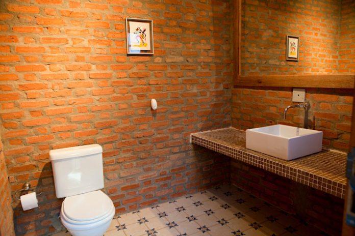 banheiro todo revestido em tijolo cru, modelo mais rústico e que com a ajuda do piso remete a tempos mais distantes, trazendo um efeito muito legal, um banheiro simples e super marcante ao mesmo tempo