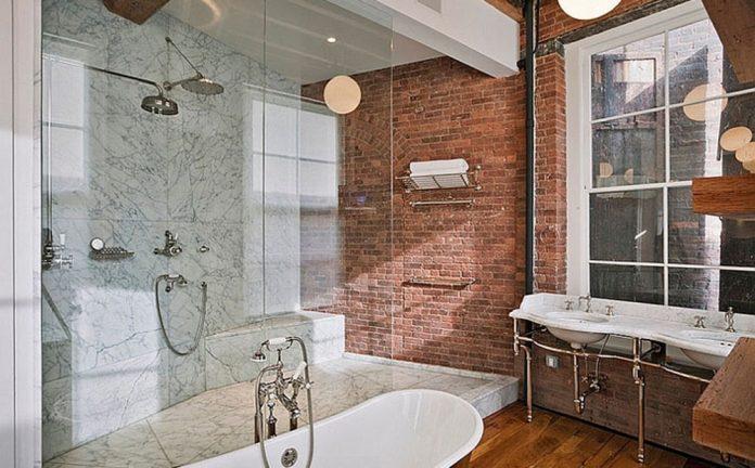 Parede em destaque no banheiro toda revestida em tijolinho