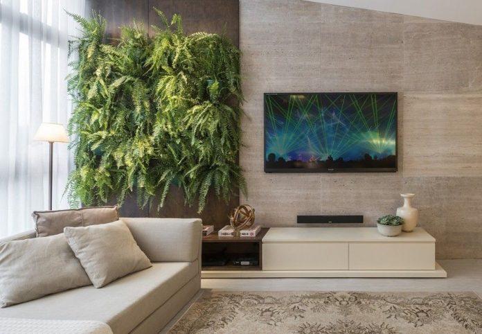 Na imagem a prateleira na sala ajuda a compor a decoração e trazer muita beleza ao local, ela fica como se fosse um painel decorativo na parede principal da sala, muito bem planejado.