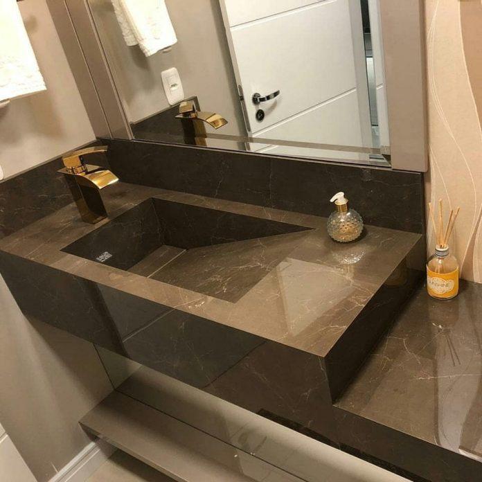 bancada esculpida, de um tom mais escuro que trouxe muita beleza e luxo a esse banheiro